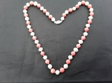 Freshwater pearl and coral necklace with sterling silver clasp. Hand knotted onto silk .